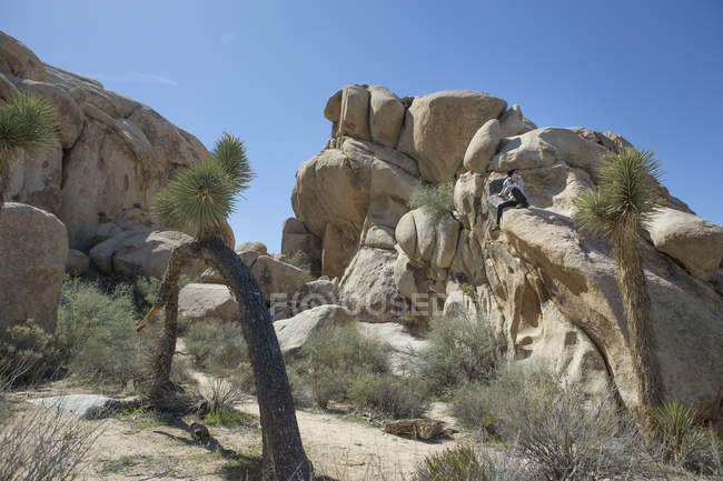 Woman sitting on large rock formation in Joshua Tree National Park, California, USA — Foto stock