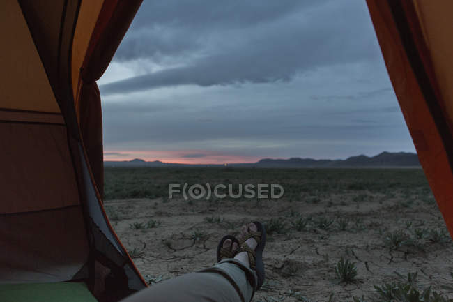 Female feet sticking out of tent at sunset in dried landscape - foto de stock