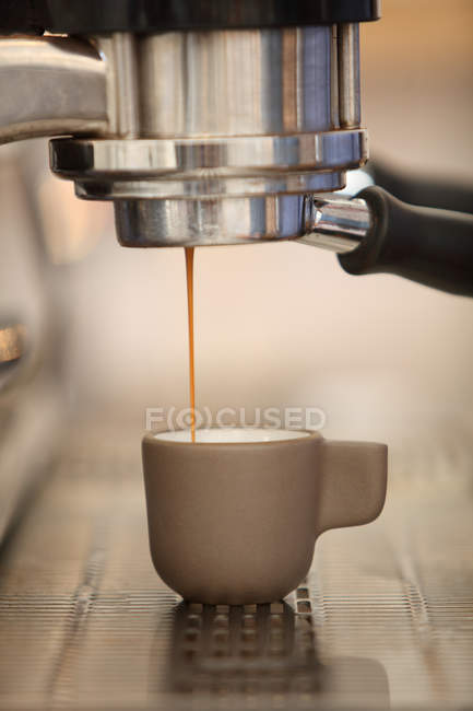 Coffee pouring into espresso cup from coffee machine — Stock Photo
