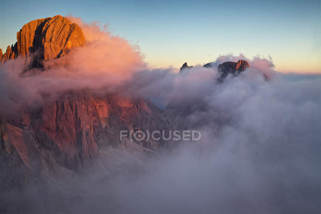 Scenic view of rocky mountain in fog and clear sky — Stock Photo