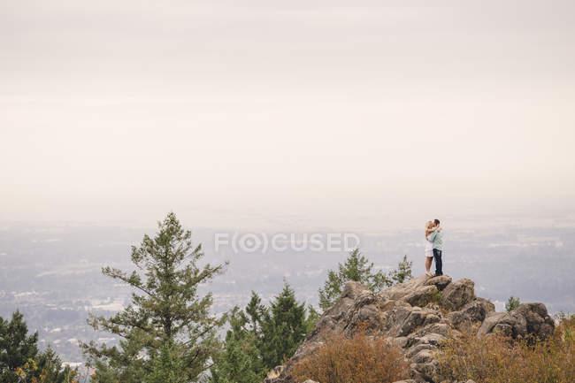 Seitenansicht eines jungen Paares, das sich tagsüber auf einem Hügel umarmt, Eugene, Oregon, USA — Stockfoto