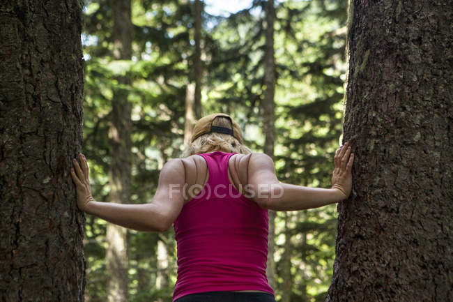 Rear view of woman in tank top standing between trees in forest, Snoqualmie, Washington State, USA — Stock Photo