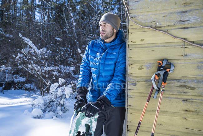 Un uomo che riposa dopo una giornata di escursioni con le ciaspole in una giornata invernale chiaro brillante — Foto stock