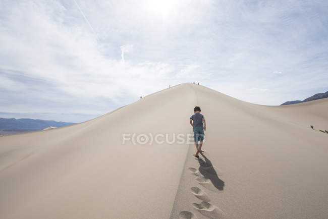 Rear view of boy walking on sand dune — Stock Photo