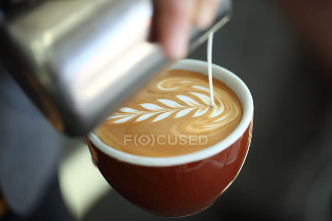 Close-up shot of barista pouring milk into cappuccino — Stock Photo