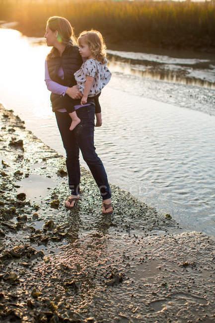 Woman carrying daughter near river bank at sunset — Stockfoto