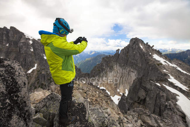Side view photograph of mountaineer photographing mountain peak in North Cascade Mountain Range, Chilliwack, British Columbia, Canada — Stock Photo