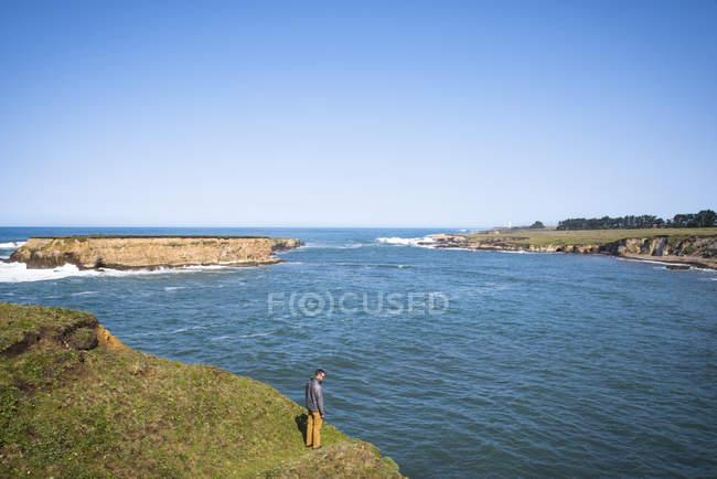 Hombre viendo las vistas de la costa en Punta Arena, California, EEUU - foto de stock