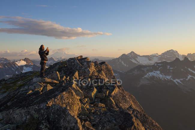 Foto des Bergsteigers am Berggipfel fotografieren Blick bei Sonnenuntergang in North Cascade Mountain Range, Chilliwack, Britisch-Kolumbien, Kanada — Stockfoto