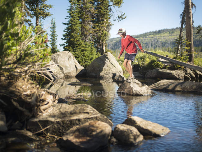 Jeune garçon sautant de la roche au-dessus du ruisseau dans le paysage normal — Photo de stock