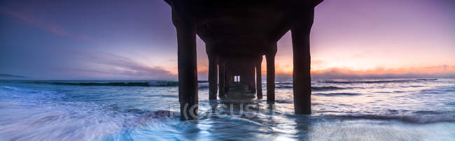 Vue panoramique du coucher du soleil depuis dessous de Manhattan Beach Pier, Los Angeles, Californie, é.-u. — Photo de stock