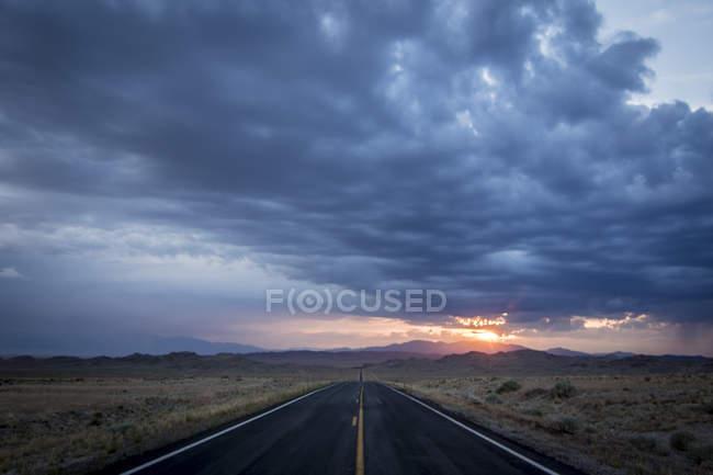 Carretera 6 desapareciendo en la distancia en el desierto en la puesta del sol, Utah, EEUU - foto de stock