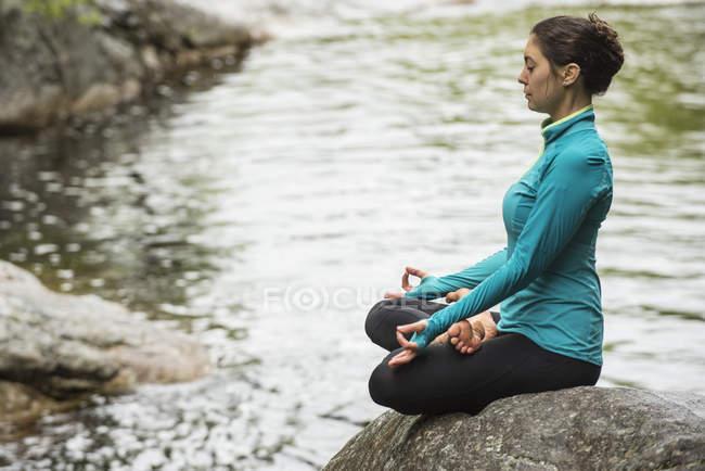 Una mujer meditando en la Pose de loto en una roca sobre un río tranquilo. - foto de stock