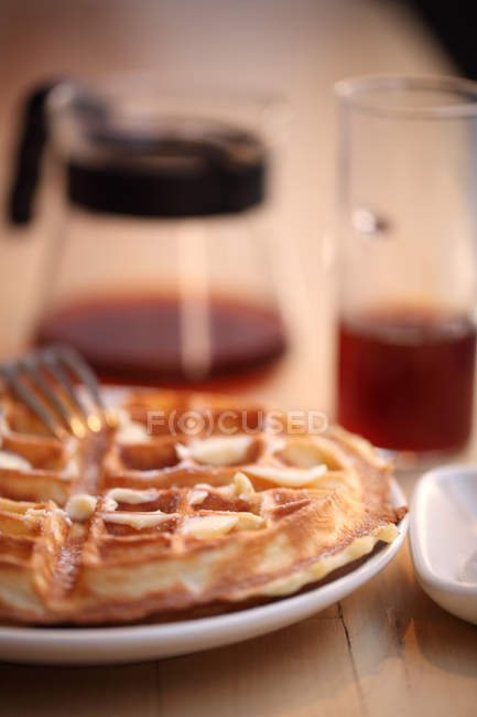 Selective focus of sweet waffles on plate with glass of juice behind — Stock Photo