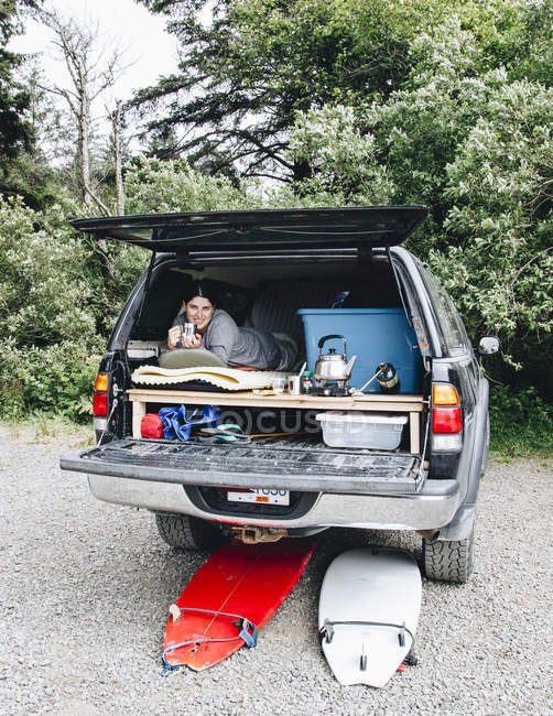 A woman on a surf trip to La Push, Washington lays in a bed in the back of her pickup truck and drinks a coffee to warm up after a surfing session. — Stock Photo