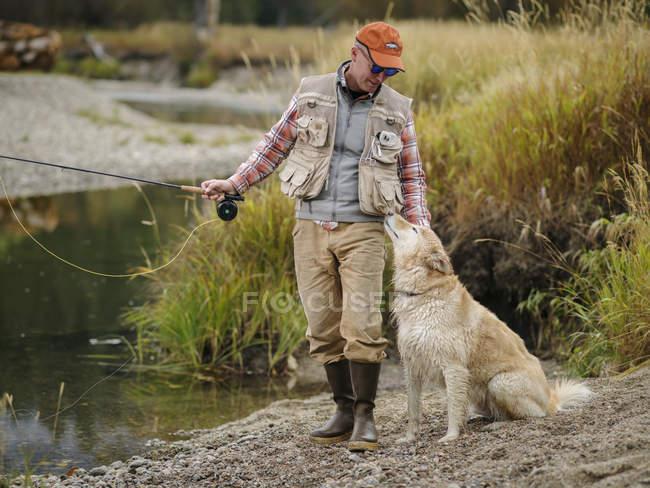 Pêche de mouche d'homme et de crabot sur la rivière — Photo de stock