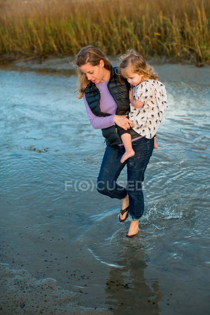 Woman walking in shallow water and carrying daughter — Stockfoto