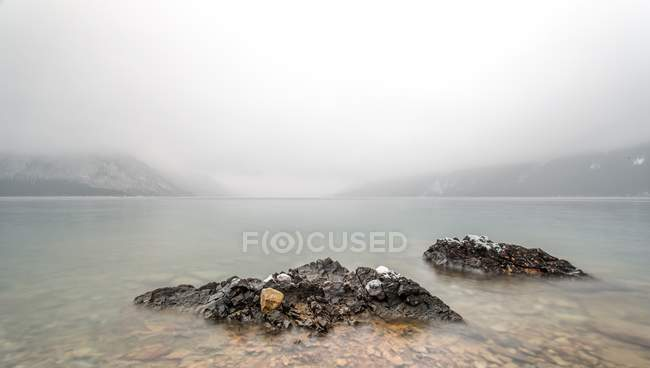 Scenic view of storm clouds over mountains and lake with two rocks on foreground — Stock Photo