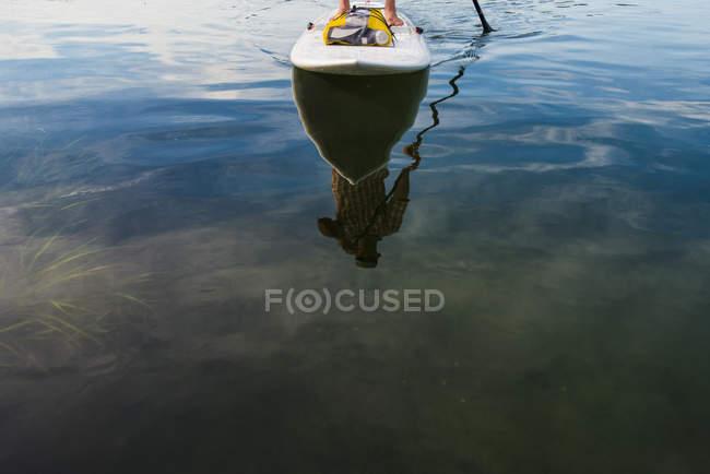 Paddleboarder masculino que reflete na superfície da água — Fotografia de Stock
