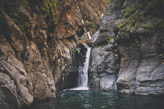 Mann Abseilen aus Wasserfall beim Canyoning in Deneau Creek, Hope, Britisch-Kolumbien, Kanada — Stockfoto