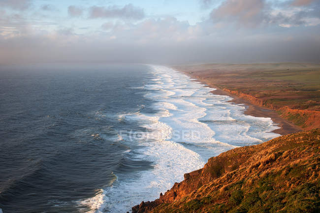 Scenic view of beautiful sunset over ocean and hills — Stock Photo