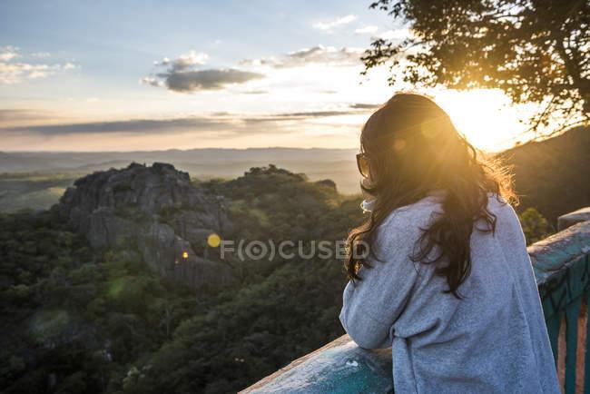 Photo de femme regardant la vision de la nature au coucher du soleil au belvédère de Mg-010 route à Serra do Parc National de l'OPIC, Minas Gerais, Brésil — Photo de stock