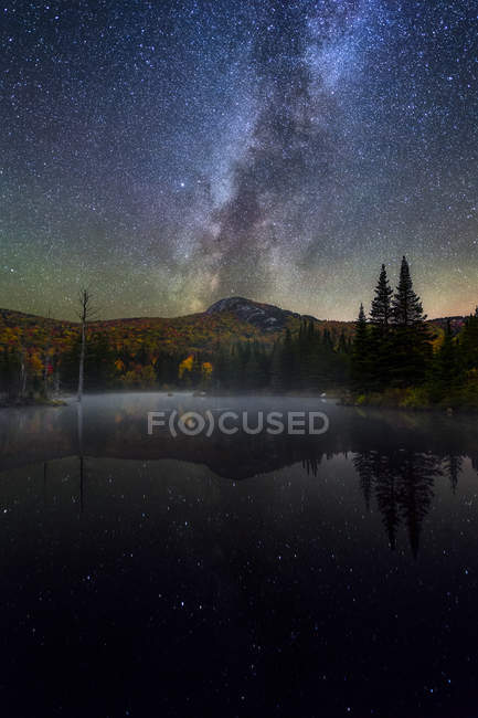Milky Way over Middle Sugarloaf Mountain and pond in New Hampshire — Stock Photo