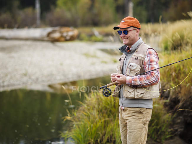 L'uomo sorridente vola pesca sul fiume — Foto stock