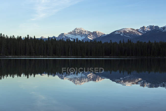 Snow capped Canadian Rockies reflected in Annette Lake at dusk in Japser National Park, Alberta, Canada — Stock Photo