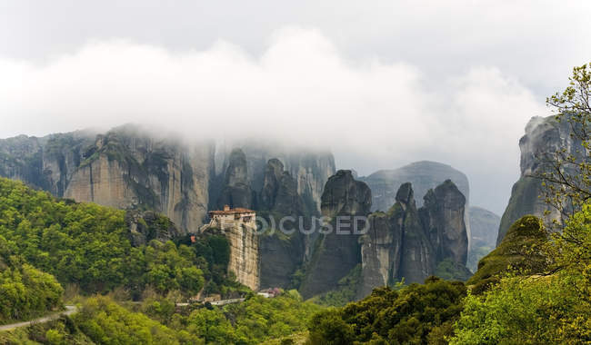 Scenic view of rocky mountains and green plants in fog — Stock Photo