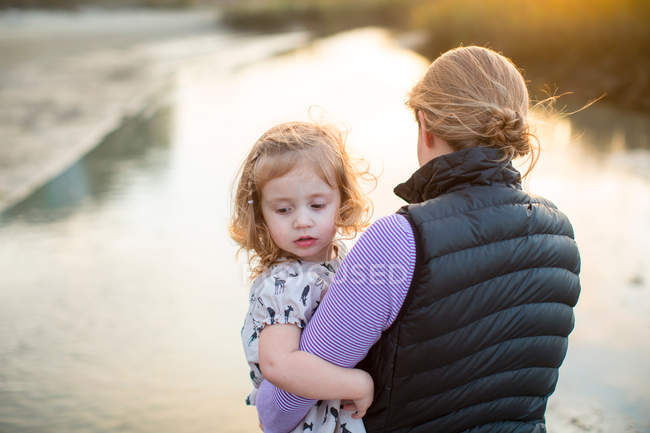 Woman carrying daughter in arms beside river — Stockfoto