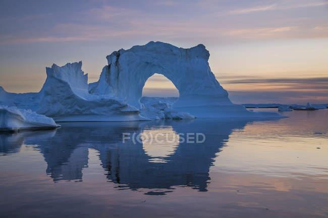 Природні arch підносяться айсберга, що відображають на поверхні води в сутінках, Гренландія — стокове фото