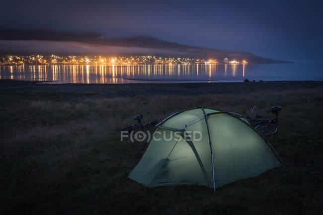Habitées tente sur la plage herbeuse, éclairé de l'intérieur, sur les rives de l'océan, à l'intérieur d'un fjord — Photo de stock