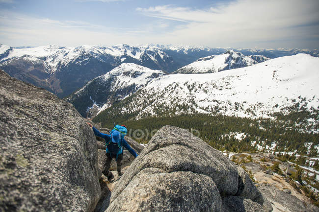 Backpacker climbing rocks while hiking to Needle Peak in winter, Hope, British Columbia, Canada — Stock Photo