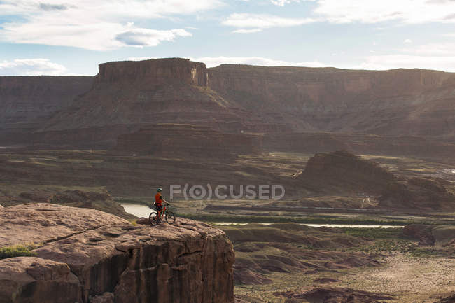Вид збоку людини з велосипеда стоячи на горі в Moab, штат Юта, США — стокове фото