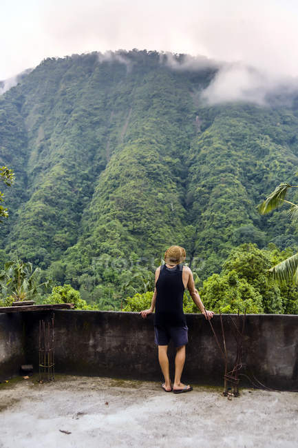Rear view of man in tank top and shorts looking at view of mountain, Kintamani, Bali, Indonesia — Stock Photo