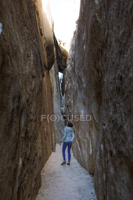 Woman standing in crevasse in Joshua Tree National Park, California, USA — Photo de stock