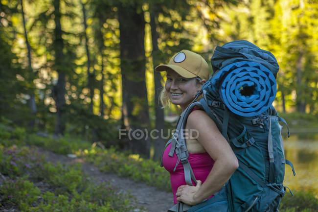 Seitenansicht einer lächelnden Frau mit Rucksack, die tagsüber im Wald steht, snoqualmie, USA — Stockfoto
