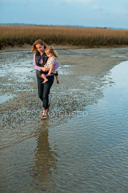 Woman carrying daughter near shallow water — Stockfoto