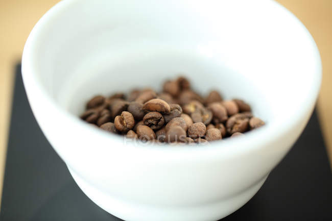 Close-up shot of roasted coffee beans in cup — Stock Photo