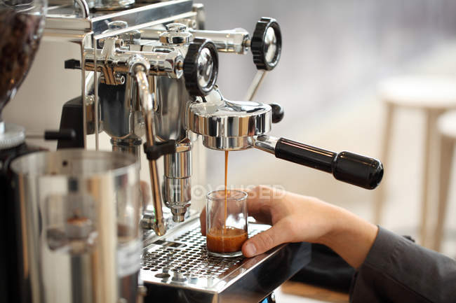 Cropped shot of barista holding glass cup while coffee pouring into it from coffee maker — Stock Photo