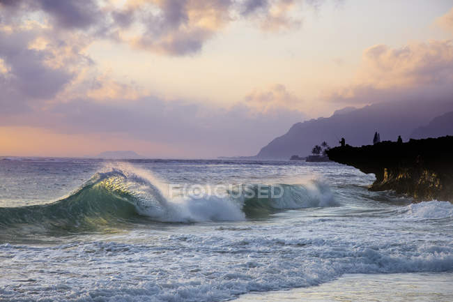 Wave breaking toward shore during sunrise at Pounder's Beach, on the East side of Oahu, Hawaii — Stock Photo