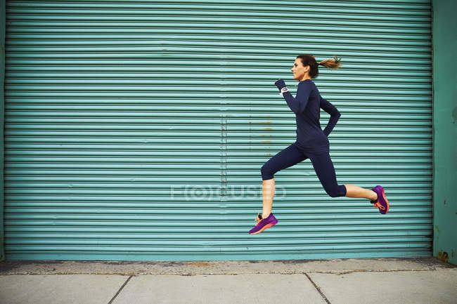 Female jogger running and jumping against green wall, Boston, Massachusetts, USA — Stock Photo