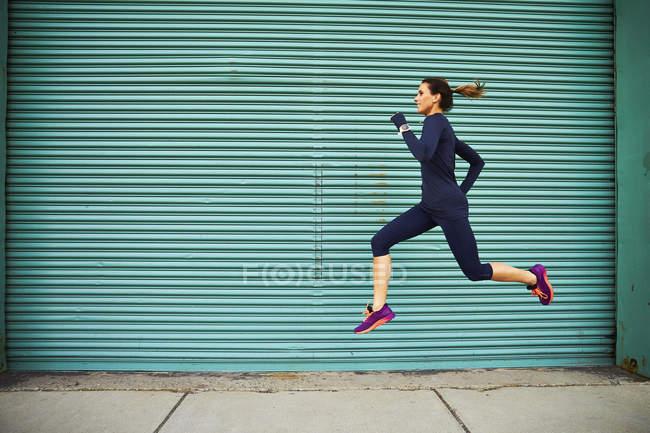 Female jogger course et le saut contre le mur végétalisé, Boston, Massachusetts, é.-u. — Photo de stock