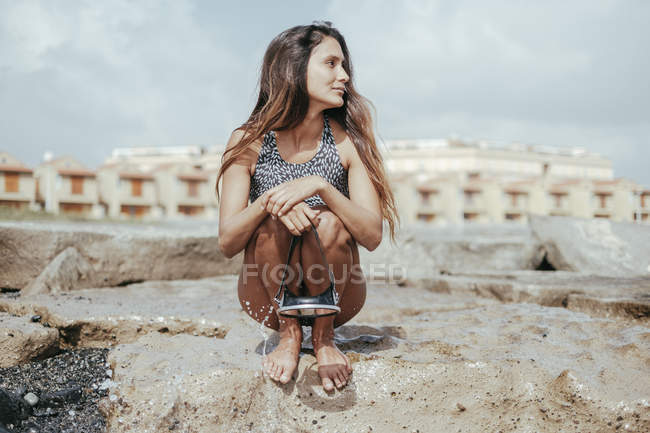 Attractive young woman in swimsuit holding diving goggles on sandy beach, Tenerife, Canary Islands, Spain — Stock Photo