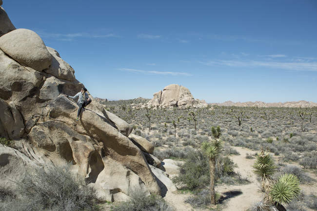 Woman sitting on rock formation in Joshua Tree National Park, California, USA — Photo de stock