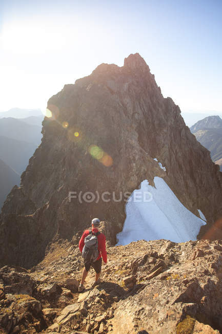 Rear view of backpacker approaching summit of Tomyhoi Peak, North Cascades National Park, Washington State, USA — Stock Photo