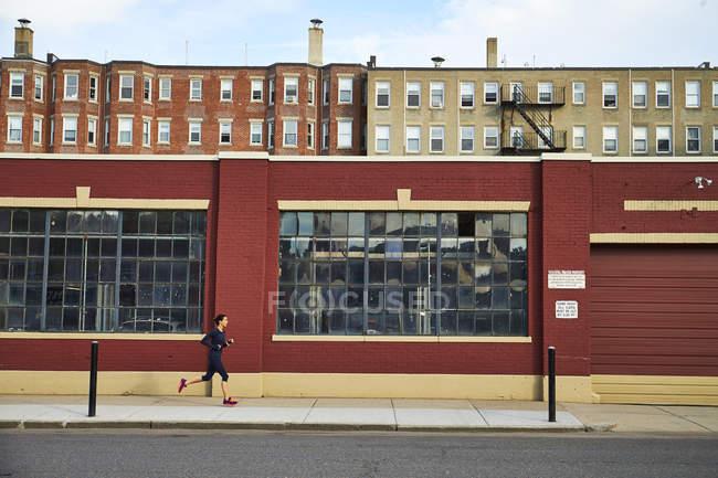 Жіночий бігун працює на тротуарі поруч засклені вікна стороні вулиці, будівництво, Бостон, штат Массачусетс, США — стокове фото
