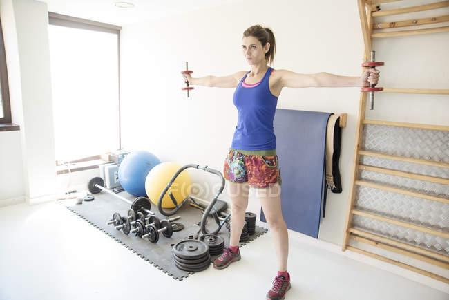 Frau anhebende Gewichte im Fitnessstudio — Stockfoto