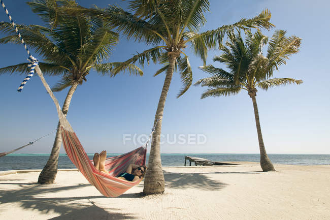Young woman relaxing in hammock on beach with view of ocean horizon — Stock Photo